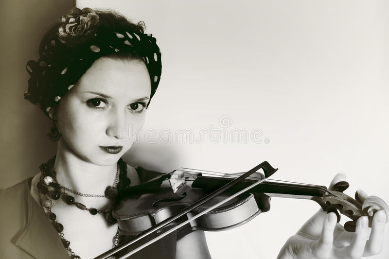 Young woman with violin on light background stock image