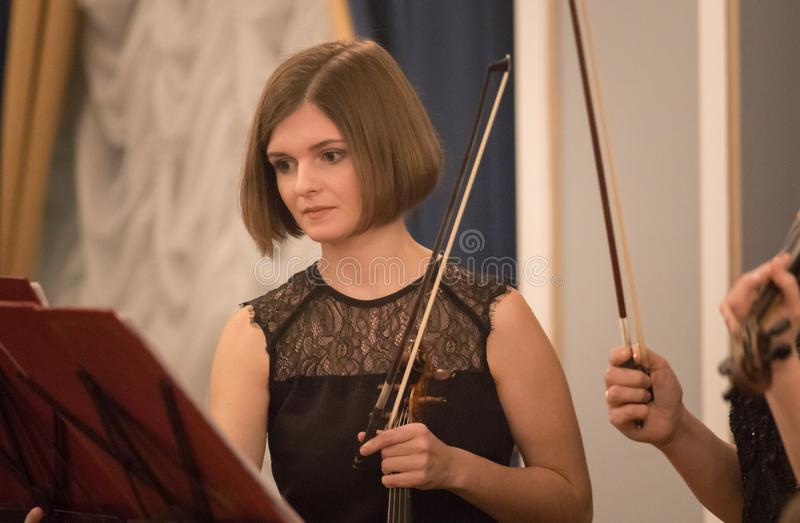 A young woman violinist holding a bow - a concert royalty free stock photos