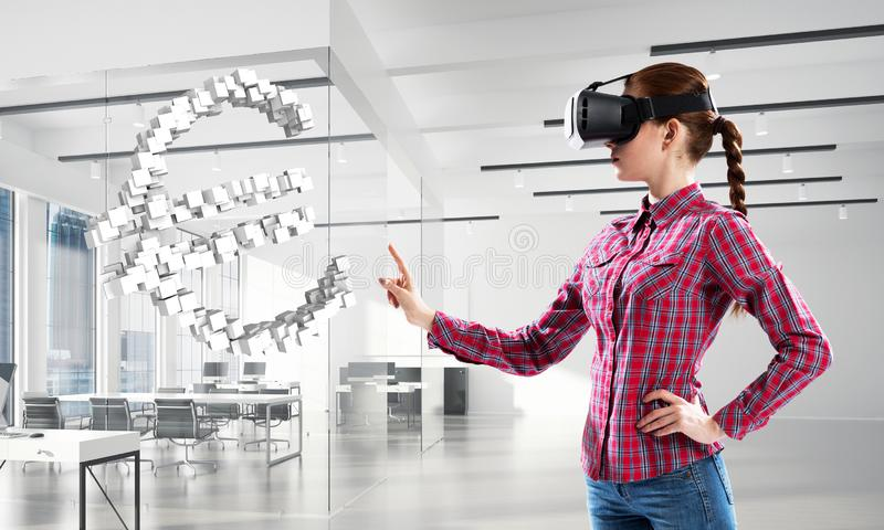 Girl in virtual reality mask experiencing virtual technology world. Mixed media stock photo