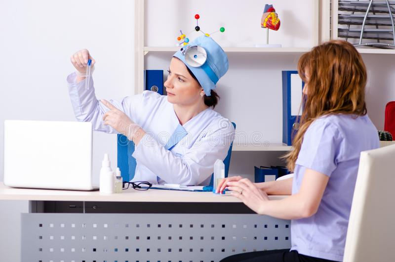 Young woman visiting female doctor otolaryngologist stock photography