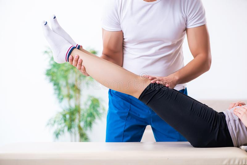 Young woman visiting male doctor physiotherapist stock image