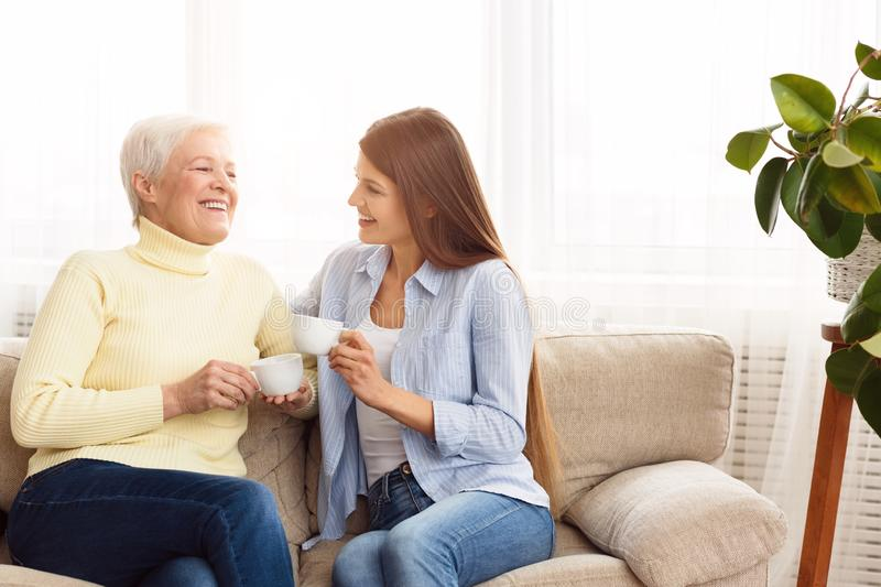 Young woman visiting senior mother and drinking coffee together stock photography