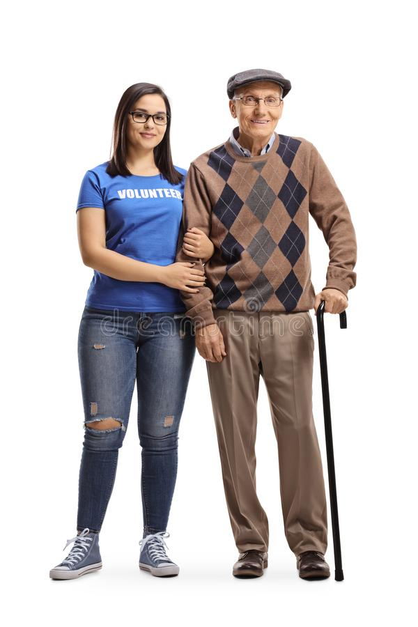 Young woman volunteer standing with a senior male pensioner with a walking cane. Full length portrait of a young women volunteer standing with a senior male stock image