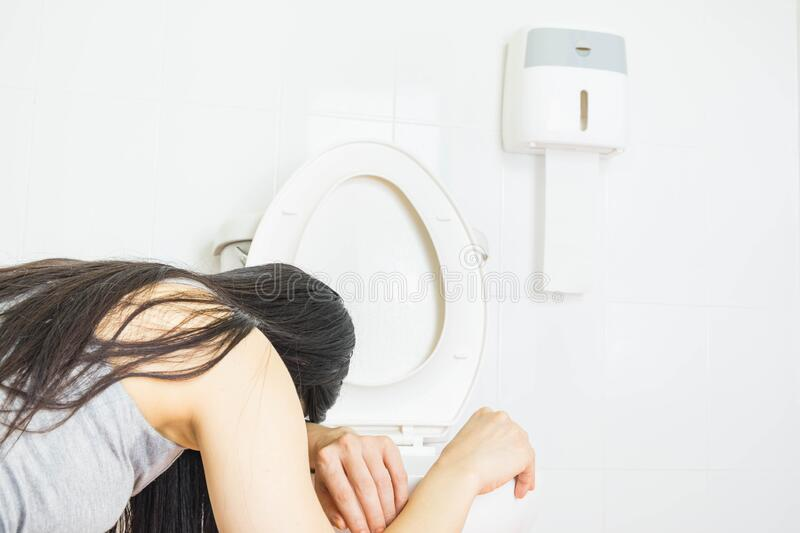 Young woman vomiting into the toilet bowl in the early stages of pregnancy or after a night of partying and drinking. Health care stock photography