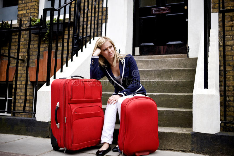 A young woman waiting on her doorstep with her suitcases royalty free stock photography