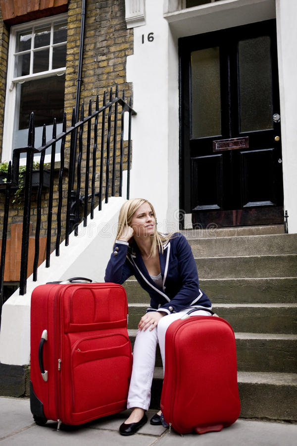 A young woman waiting on her doorstep with her suitcases stock photo