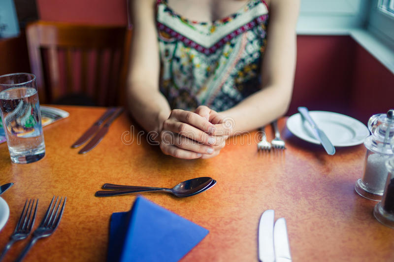 Young woman waiting for her lunch. A young woman is sitting in a restaurant and is waiting for her lunch royalty free stock image