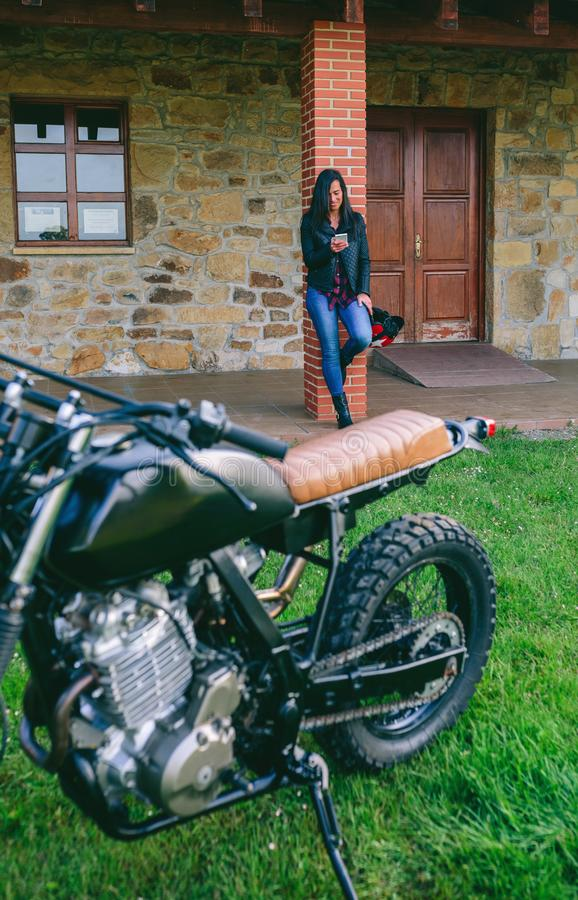 Woman waiting looking at the mobile with custom motorcycle. Young woman waiting looking at the mobile with custom motorcycle in the foreground. Selective focus royalty free stock photo