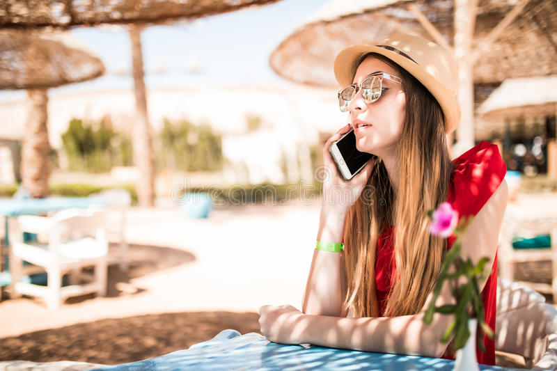 Young woman waiting for order and speak on phone in the restaurant near the sea. Summer vocation royalty free stock photography