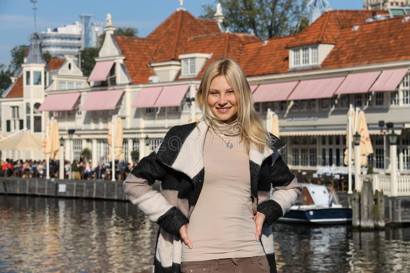 Young woman waiting for tour boat in Amsterdam, the Netherlands stock image