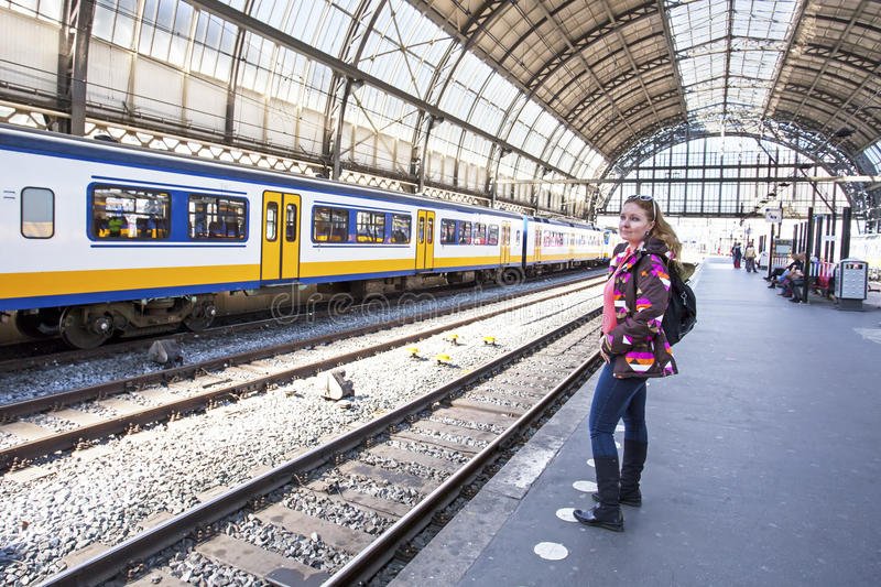 Young woman waiting for the train at central station Amsterdam stock photography