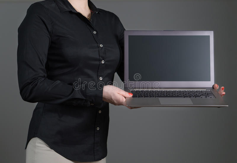 Young woman or waitress showing laptop screen stock photography