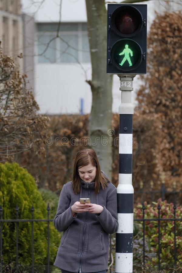 Young woman looks at her cellphone and does not pay attention to stock images