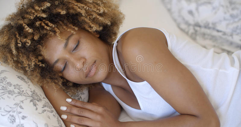 Young Woman Waking Up From Sleep And Smiling. Attractive young african-american woman wakes up in her bedroom royalty free stock photos
