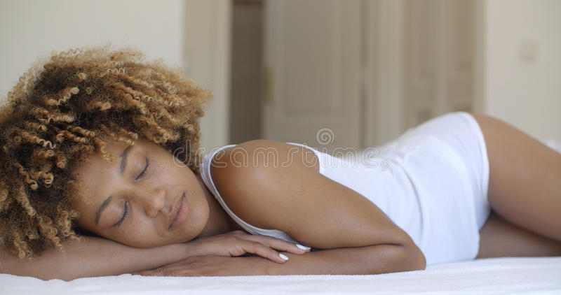 Young Woman Waking Up From Sleep And Smiling. Attractive young african-american woman wakes up in her bedroom stock images