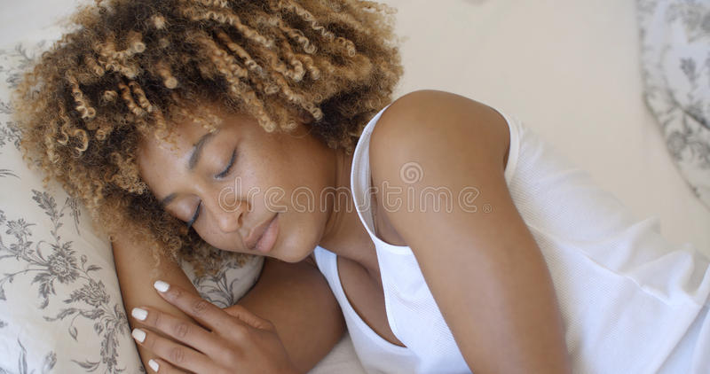 Young Woman Waking Up From Sleep And Smiling. Attractive young african-american woman wakes up in her bedroom royalty free stock image