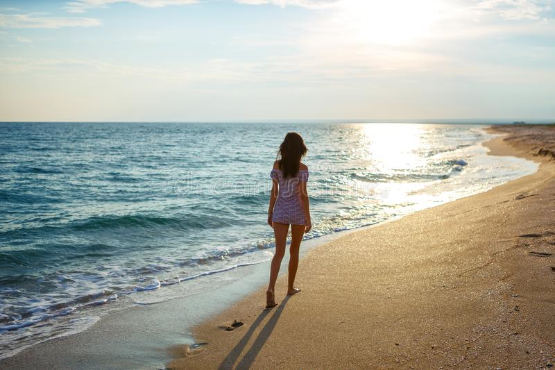 Young woman walk on an empty wild beach towards celestial beams of light falling from the sky,. The concept of travel and tourism, leisure at sea stock photos