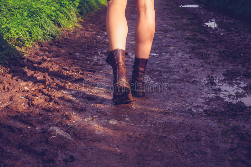 Young woman walking along muddy trail royalty free stock image