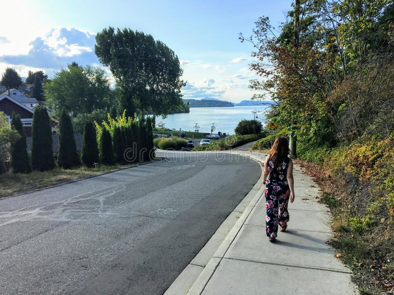 A young woman walking along the sidewalk towards the ocean in the distance. It is a beautiful neighbourhood on a pretty sunny day royalty free stock image