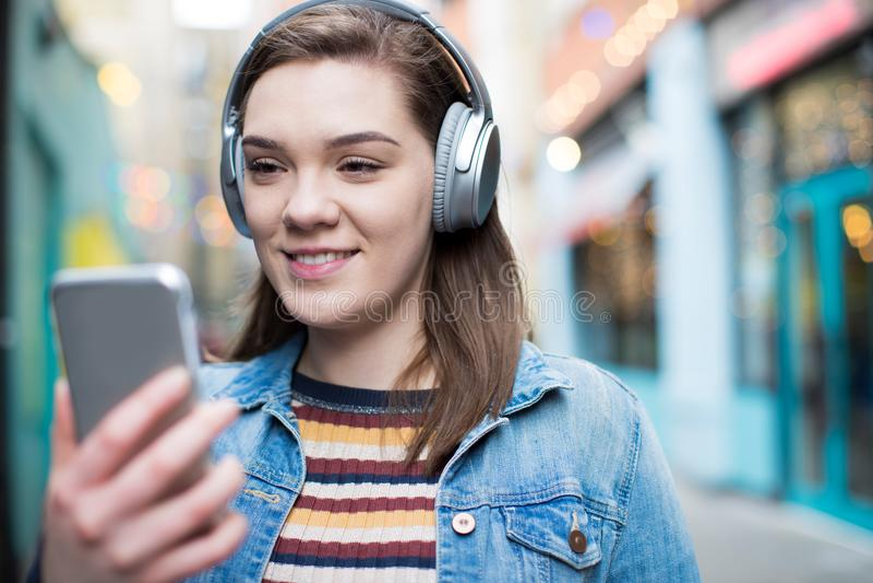 Young Woman Walking Along Street Streaming Music From Mobile Phone. Woman Walking Along Street Streaming Music From Mobile Phone stock photo