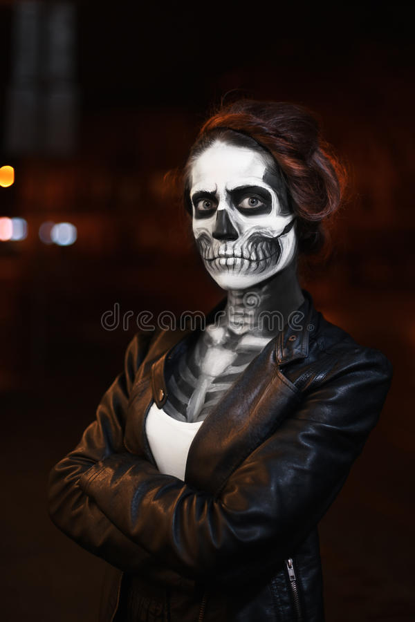 Young woman walking on avenue. Face art for Halloween party. Street portrait. Waist up. Night city background royalty free stock photos