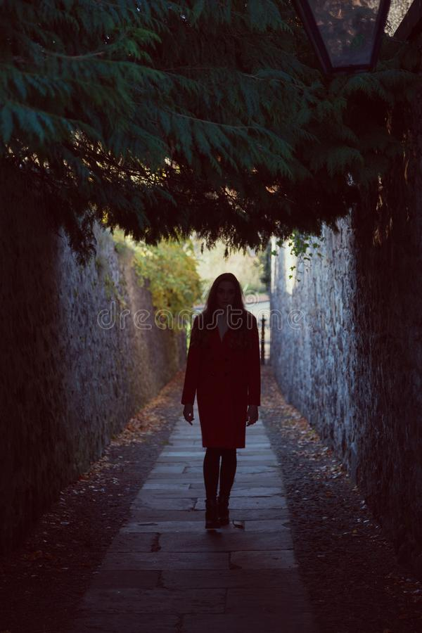 Woman waling away down a dark alley. A young woman walking away from us down a dark alley. She is confronting her fears, or taking on a challenge. She could also royalty free stock images