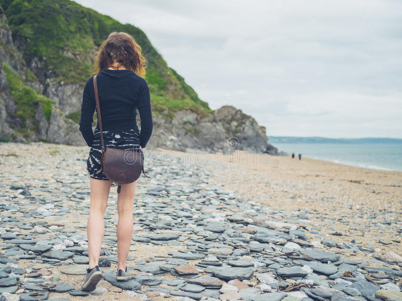 Young woman walking on the beach. A young woman is walking on the beach royalty free stock images