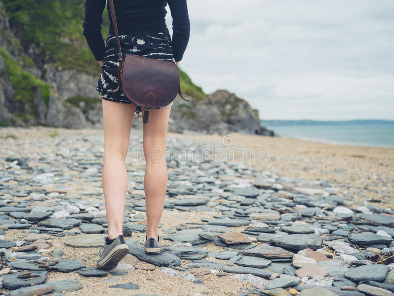 Young woman walking on the beach. A young woman is walking on the beach royalty free stock photos