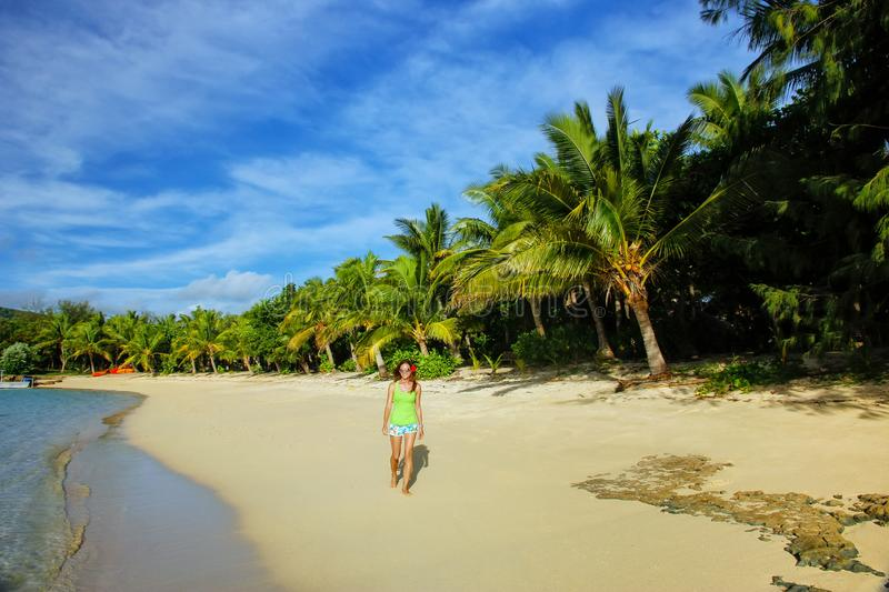 Young woman walking on a beach on Drawaqa Island, Yasawa Islands, Fiji. This archipelago consists of about 20 volcanic islands stock photography