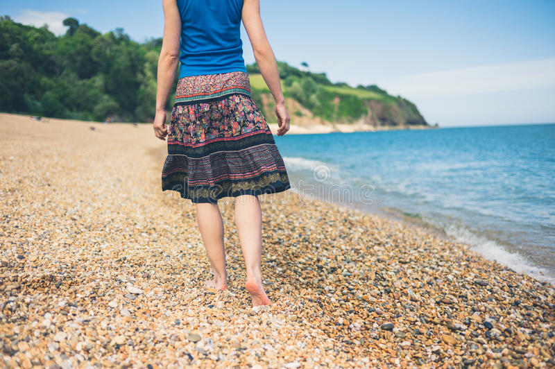 Young woman walking on the beach. A young woman is walking on the beach in the summer royalty free stock photo