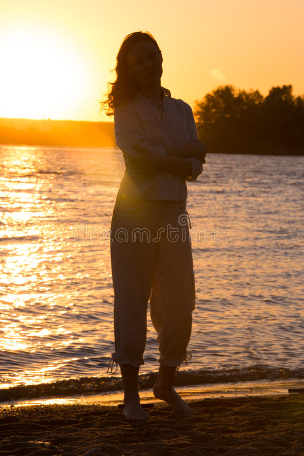 Young woman walking on beach under sunset light. Full length portrait royalty free stock photography