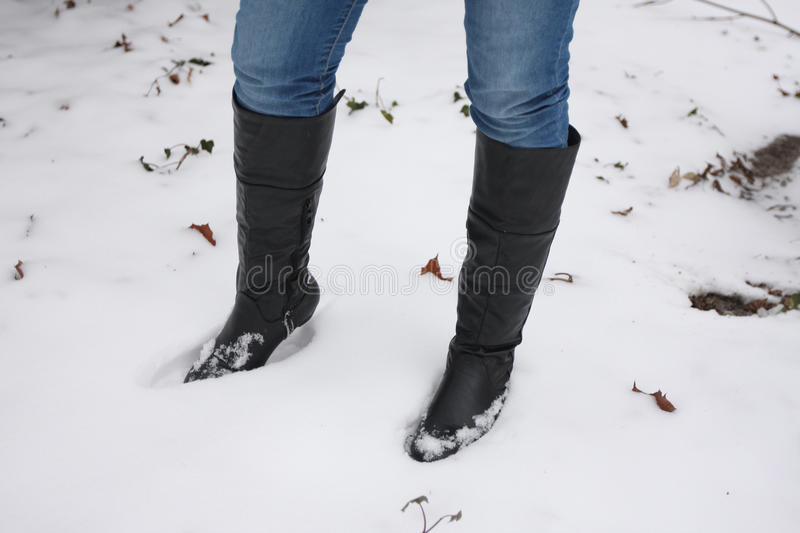 Young woman walking boots in the snow. Young woman wears Jeans with black walking boots in the snow royalty free stock images