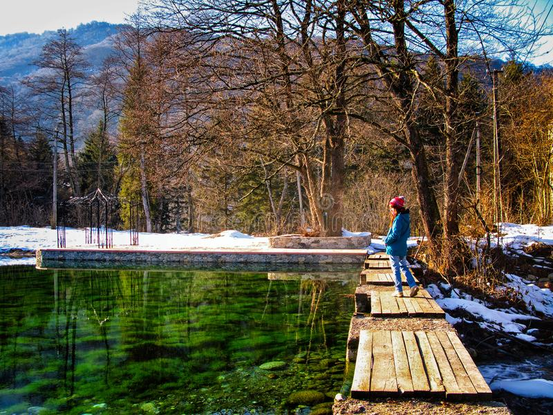Young woman walking on bridge at autumn landscape. Young girl walking on old wooden bridge. Autumn or winter sunny day. Panoramic view of lake or river at forest royalty free stock photos