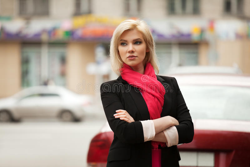 Young fashion woman in black jacket walking in a city street royalty free stock images