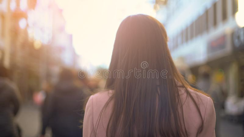 Young woman walking on crowded shopping street, touristic destination, back view. Stock photo royalty free stock photos
