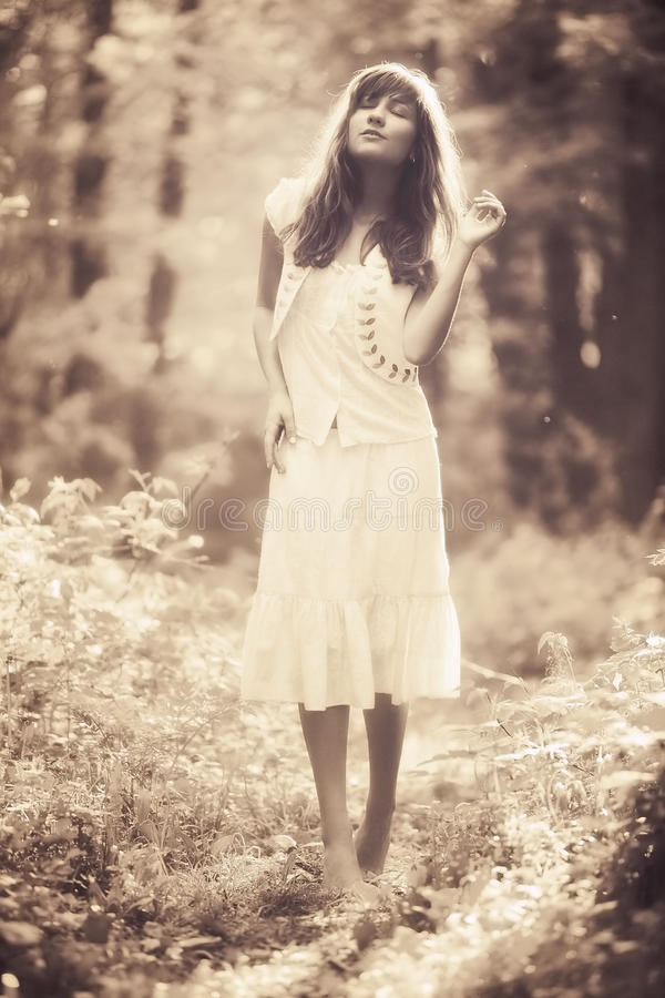 Young woman walking in a forest. Sepia retro colors stock photos