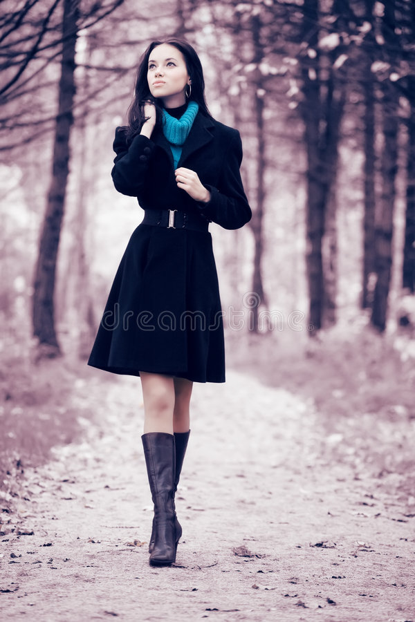 Young woman walking in forest. Soft pink and blue tint royalty free stock images