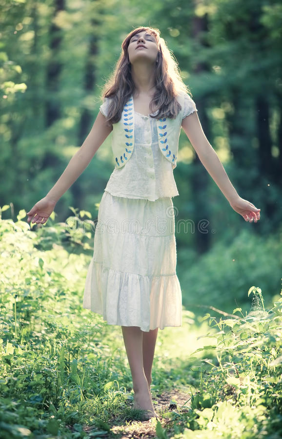Young woman walking in a forest. Delighting good weather stock image