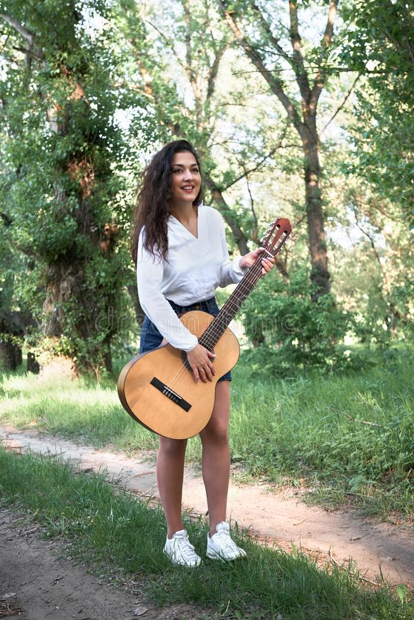 Young woman walking in the forest and playing guitar, summer nat. Ure, bright sunlight, shadows and green leaves, romantic feelings stock photography