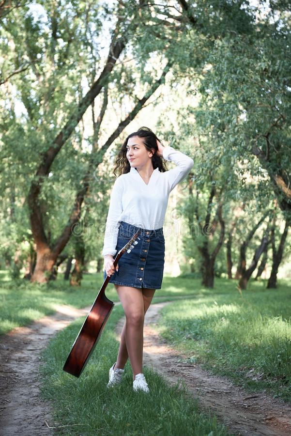 Young woman walking in the forest and playing guitar, summer nature, bright sunlight, shadows and green leaves, romantic feelings stock photos