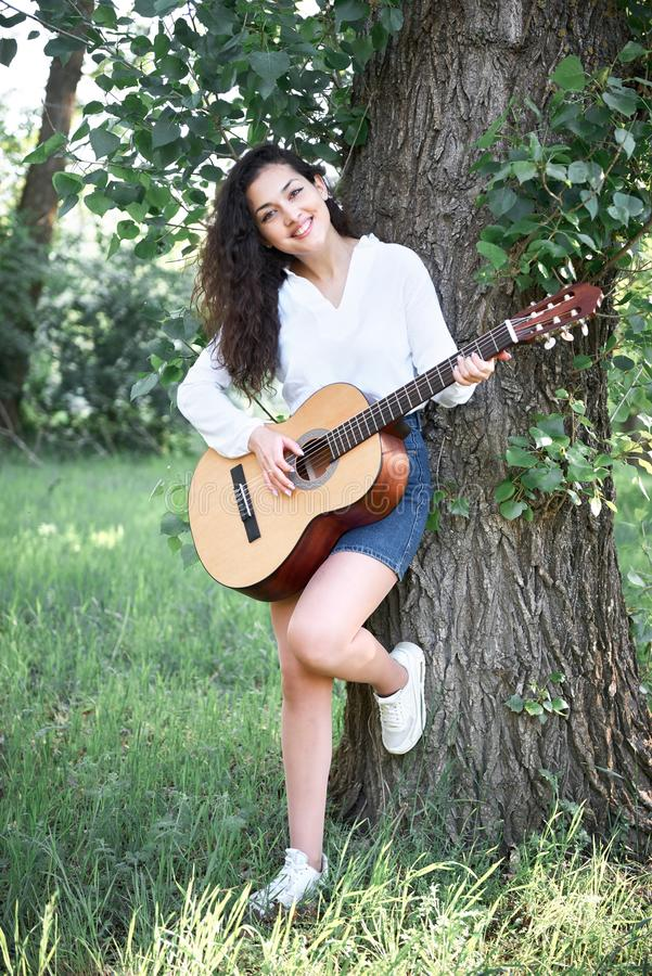 Young woman walking in the forest and playing guitar, summer nature, bright sunlight, shadows and green leaves, romantic feelings stock image