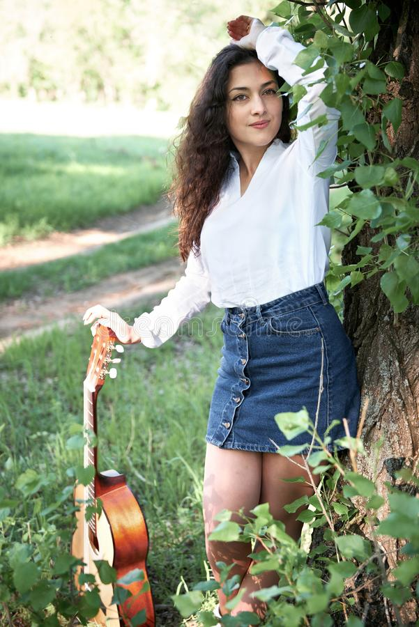 Young woman walking in the forest and playing guitar, summer nature, bright sunlight, shadows and green leaves, romantic feelings stock photo