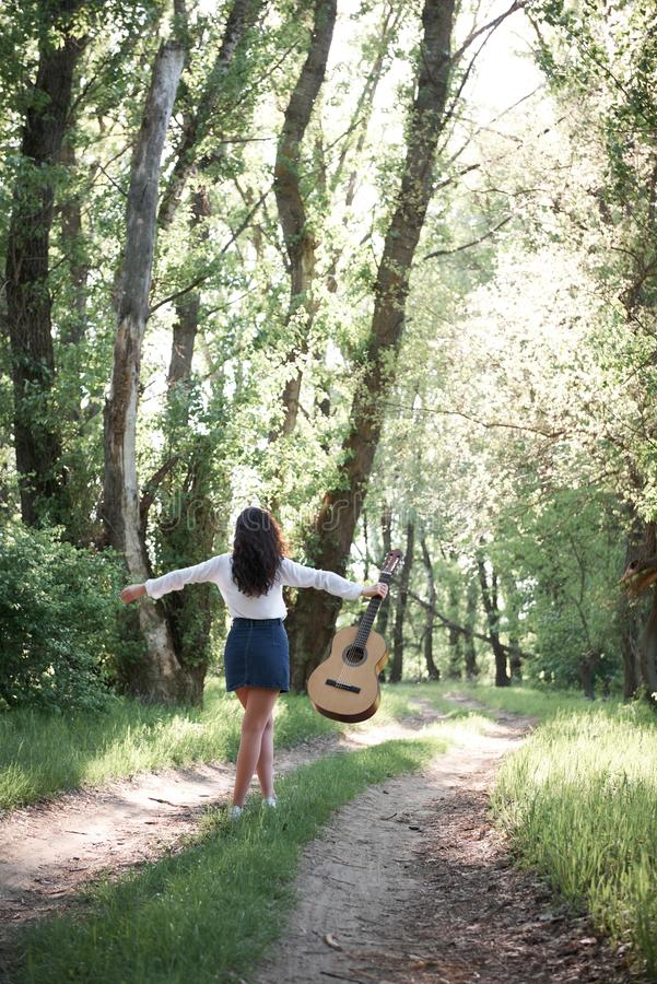 Young woman walking in the forest and playing guitar, summer nature, bright sunlight, shadows and green leaves, romantic feelings royalty free stock image