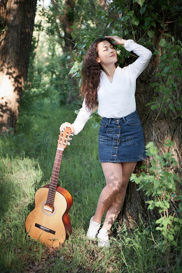 Young woman walking in the forest and playing guitar, summer nature, bright sunlight, shadows and green leaves, romantic feelings stock images