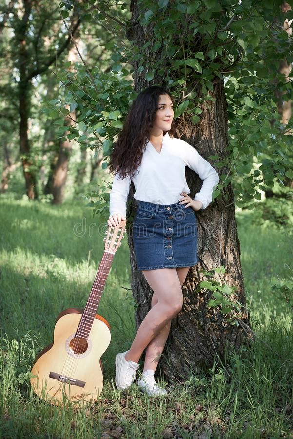 Young woman walking in the forest and playing guitar, summer nature, bright sunlight, shadows and green leaves, romantic feelings royalty free stock photo