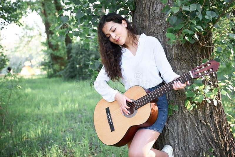 Young woman walking in the forest and playing guitar, summer nature, bright sunlight, shadows and green leaves, romantic feelings royalty free stock photos