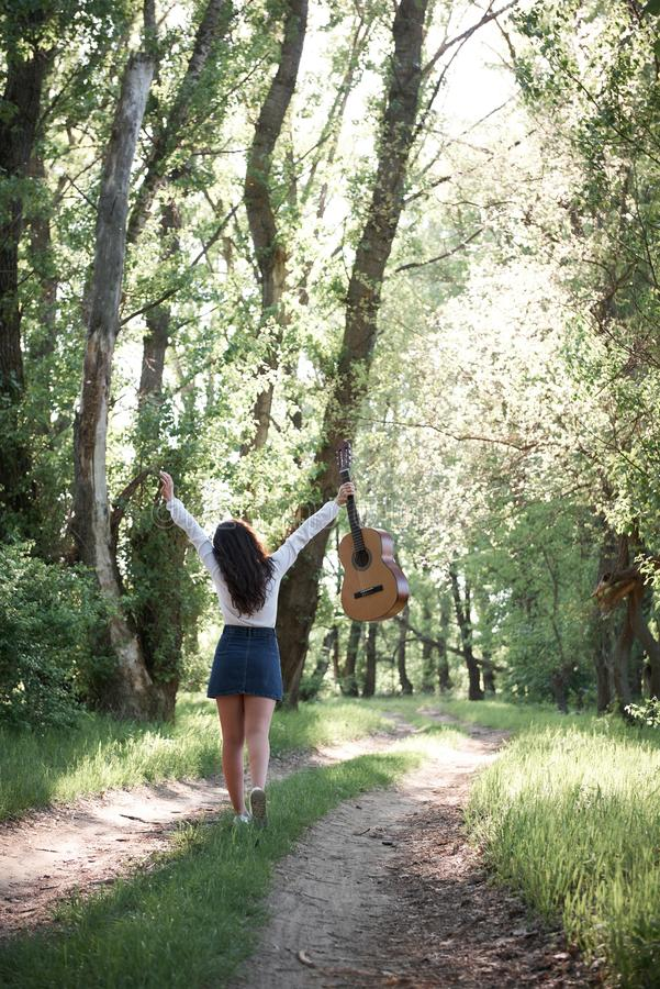 Young woman walking in the forest and playing guitar, summer nature, bright sunlight, shadows and green leaves, romantic feelings royalty free stock photography