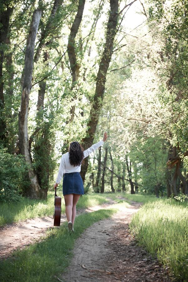 Young woman walking in the forest and playing guitar, summer nature, bright sunlight, shadows and green leaves, romantic feelings royalty free stock images