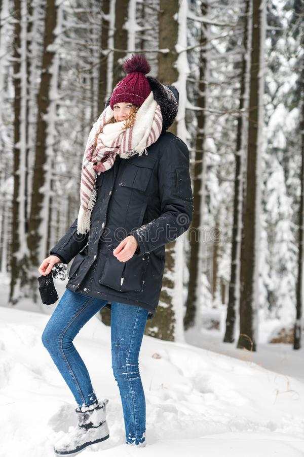A young woman is walking in the forest. In winter time with lots of snow royalty free stock image