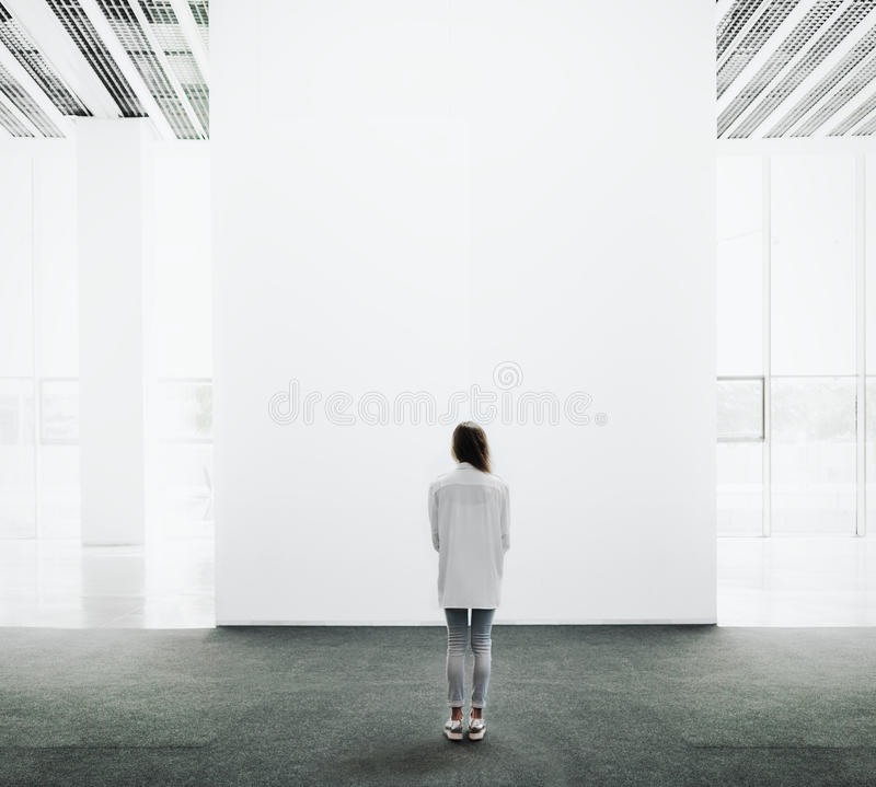 Young woman walking through a gallery and looking royalty free stock images